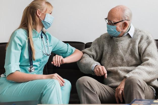 Weiblicher krankenschwester-ellbogen, der alten mann während der pandemie berührt