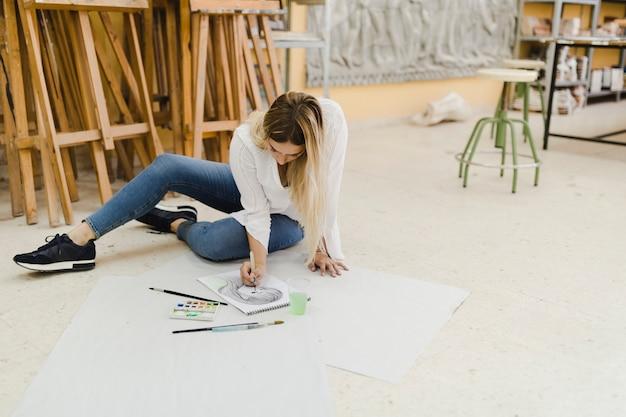 Weiblicher künstler, der auf bodenmalereiskizze auf papier sitzt