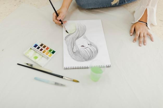 Weiblicher künstler, der auf weiblicher gesichtsskizze malt