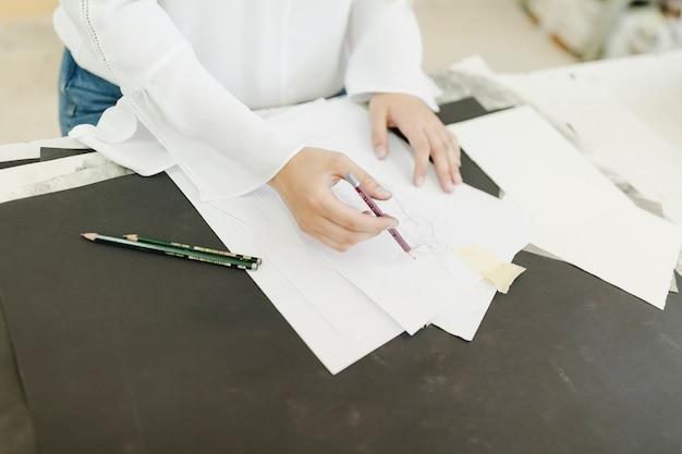 Weiblicher künstler, der auf weißbuch mit bleistift auf tabelle skizziert