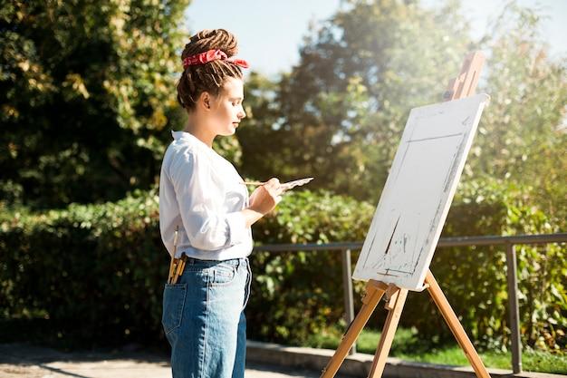 Weiblicher künstler, der draußen malt