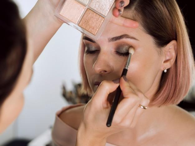 Weiblicher künstler, der make-up auf modell anwendet