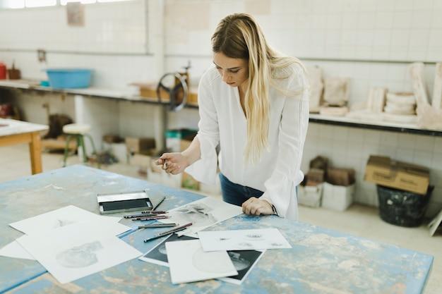 Weiblicher künstler, der mit skizzen auf weißbuch arbeitet