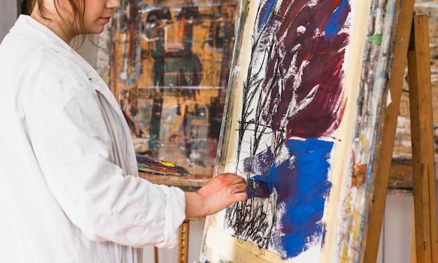 Weiblicher künstlermalerei mit bürste auf segeltuch an der werkstatt