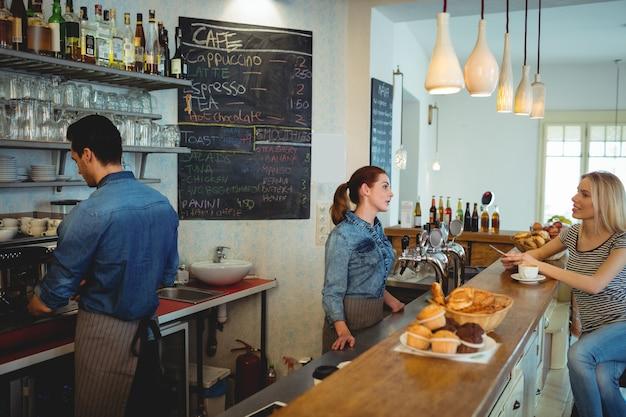 Weiblicher kunde, der mit barista am café spricht