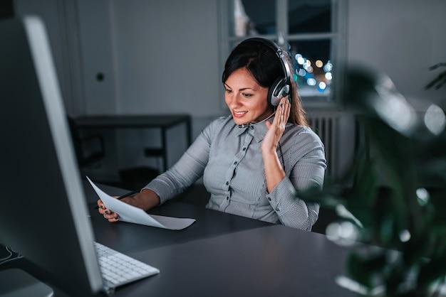 Weiblicher kundenbetreuungsbetreiber, der nachtschicht in call-center bearbeitet.