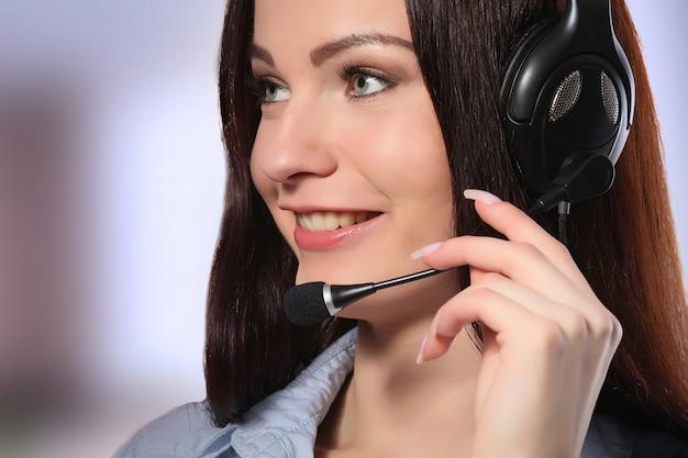 Weiblicher kundenbetreuungsbetreiber mit kopfhörer und dem lächeln