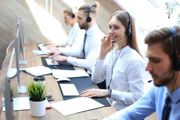 Weiblicher kundendienstmitarbeiter mit headset und lächelnd, begleitet von ihrem team.