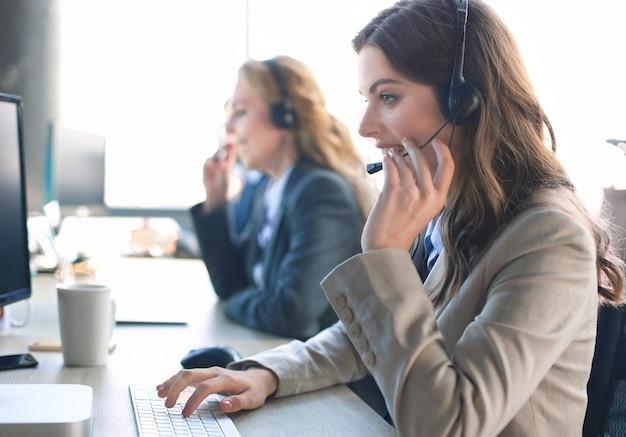 Weiblicher kundendienstmitarbeiter mit headset und lächelnd, mit kollegen im hintergrund.