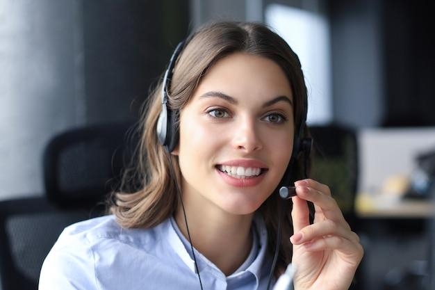 Weiblicher kundendienstmitarbeiter mit kopfhörer und lächeln.