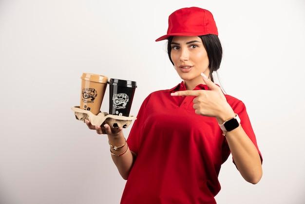 Weiblicher kurier, der auf tassen kaffee zeigt. hochwertiges foto