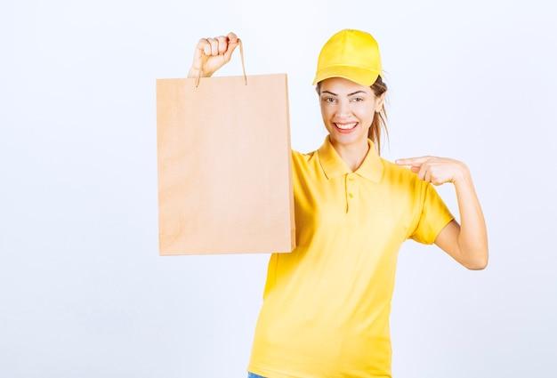 Weiblicher kurier, der eine pappeinkaufstasche hält und sich glücklich fühlt.
