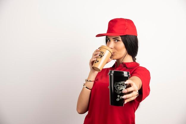 Weiblicher kurier, der eine tasse kaffee auf weißem hintergrund trinkt. hochwertiges foto