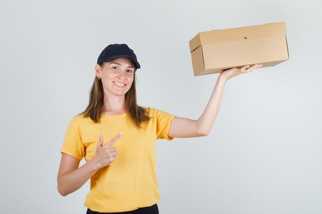Weiblicher kurier, der finger auf pappkarton in t-shirt, hose, mütze zeigt und froh aussieht