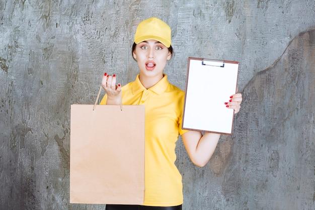 Weiblicher kurier, der gelbe uniform trägt, die eine einkaufstasche aus pappe liefert und den rohling zur unterschrift präsentiert.