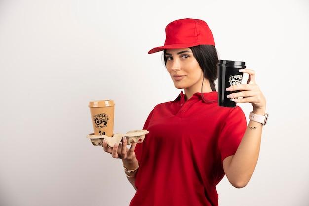 Weiblicher kurier, der kaffeetassen auf weißem hintergrund zeigt. hochwertiges foto