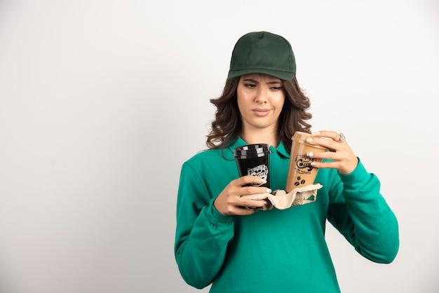 Weiblicher kurier, der kaffeetassen mit beunruhigendem ausdruck betrachtet.