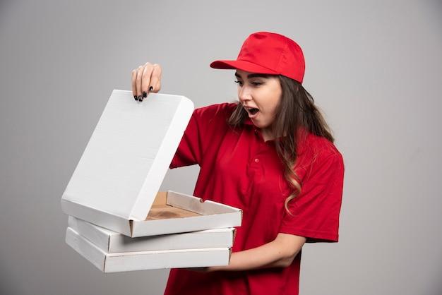 Weiblicher kurier, der leere pizzaschachtel betrachtet.