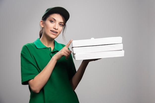 Weiblicher kurier, der mit pizzaschachteln aufwirft