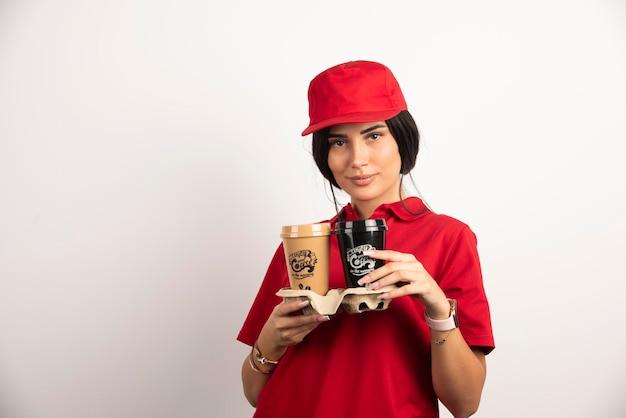Weiblicher kurier, der mit zwei tassen kaffee aufwirft. hochwertiges foto