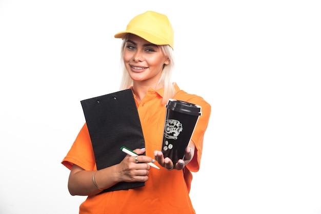 Weiblicher kurier, der notizbuch hält und eine tasse kaffee auf weißem hintergrund verschenkt. hochwertiges foto