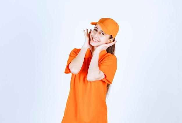 Weiblicher kurier, der orange uniform und mütze trägt.