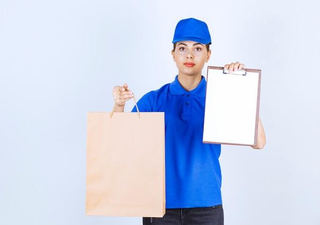 Weiblicher kurier, der papierhandwerkbeutel trägt und klemmbrett zeigt.