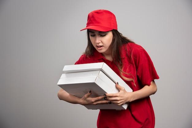 Weiblicher kurier, der pizzaschachteln auf grauer wand greift.