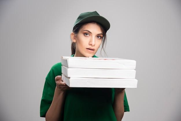 Weiblicher kurier, der pizzaschachteln hält