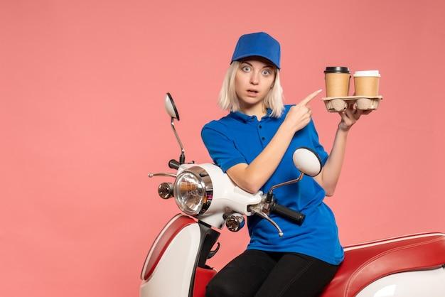 Weiblicher kurier der vorderansicht auf fahrrad mit kaffeetassen auf dem rosa