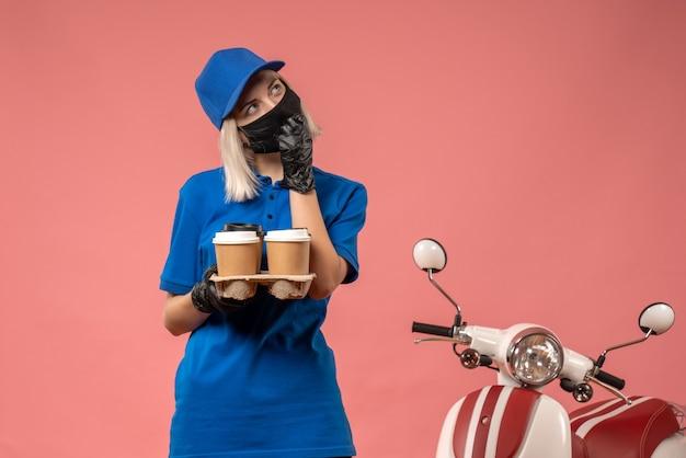 Weiblicher kurier der vorderansicht, der kaffeetassen auf dem rosa hält