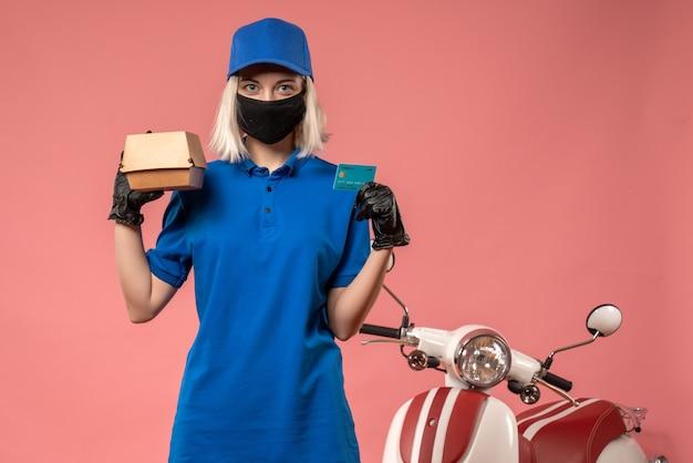 Weiblicher kurier der vorderansicht, der kleines nahrungsmittelpaket auf rosa hält