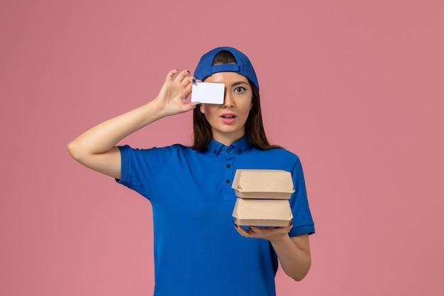 Weiblicher kurier der vorderansicht im blauen uniformumhang, der karte und kleine lieferpakete auf hellrosa wand hält, servicemitarbeiter-lieferarbeiter