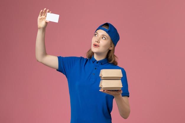 Weiblicher kurier der vorderansicht im blauen uniformumhang, der kleine liefernahrungsmittelpakete und karte auf rosa hintergrunddienstlieferungsmitarbeiterarbeit hält