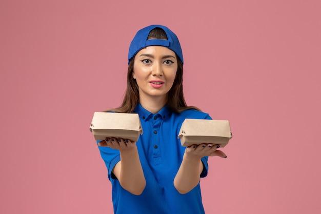 Weiblicher kurier der vorderansicht im blauen uniformumhang, der kleine lieferpakete auf rosa wand hält, mitarbeiterdienstarbeiterlieferung