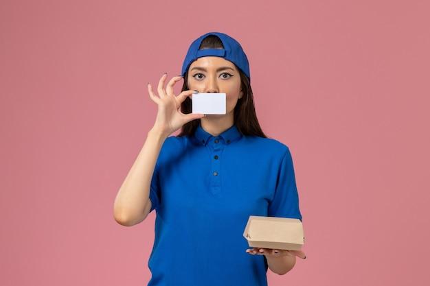 Weiblicher kurier der vorderansicht im blauen uniformumhang, der kleines lieferpaket mit plastikkarte auf hellrosa wand hält, mitarbeiterarbeitsjobdienstlieferung