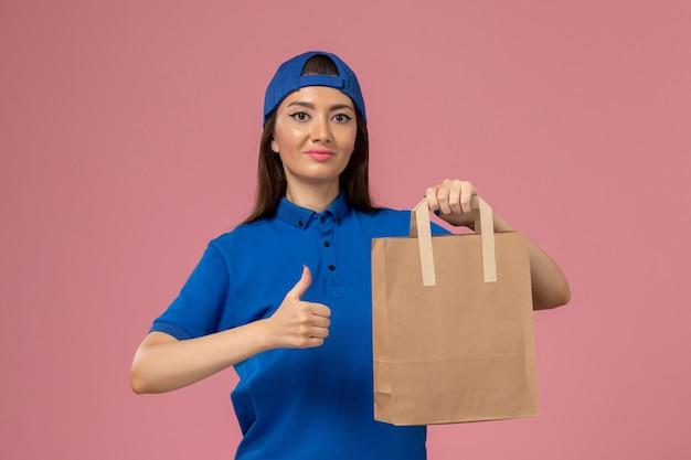 Weiblicher kurier der vorderansicht im blauen uniformumhang, der lieferpapierpaket an der rosa wand hält, servicemitarbeiter, der arbeit liefert