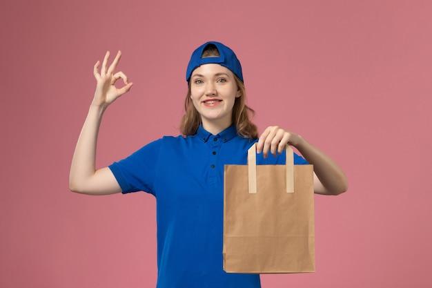 Weiblicher kurier der vorderansicht im blauen uniformumhang, der lieferpapierpaket auf rosa wand hält, mitarbeiterdienstlieferarbeit
