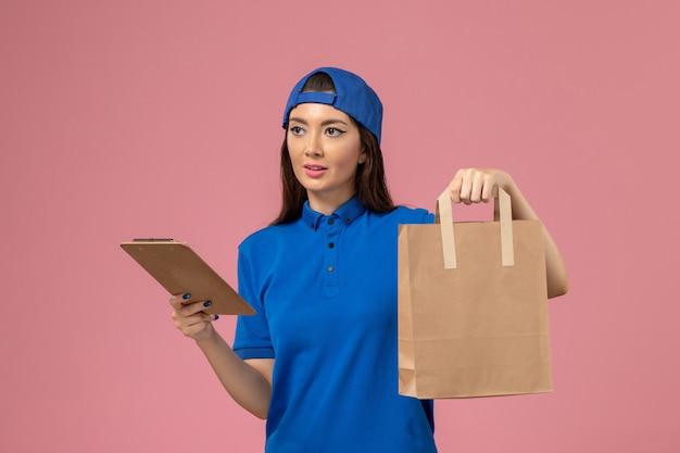 Weiblicher kurier der vorderansicht im blauen uniformumhang, der lieferpapierpaket und notizblock auf der rosa wand hält, servicemitarbeiter, der arbeit liefert