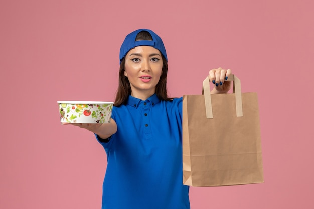 Weiblicher kurier der vorderansicht im blauen uniformumhang, der lieferpapierpaket und -schale auf rosa wand hält, dienstmitarbeiterjobarbeit liefert