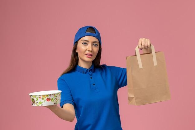 Weiblicher kurier der vorderansicht im blauen uniformumhang, der lieferpapierpaket und schüssel auf rosa wand hält, servicemitarbeiter, der arbeit liefert