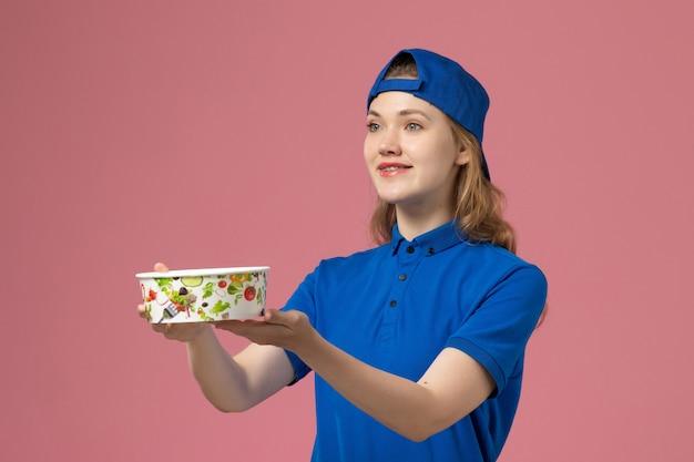 Weiblicher kurier der vorderansicht im blauen uniformumhang, der lieferschüssel auf dem rosa schreibtischdienstliefermitarbeiter hält