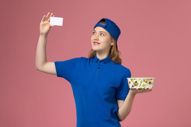 Weiblicher kurier der vorderansicht im blauen uniformumhang, der lieferschüssel mit karte auf hellrosa wand hält, service delivery-mitarbeiter