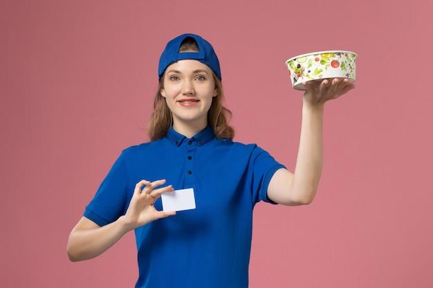 Weiblicher kurier der vorderansicht im blauen uniformumhang, der lieferschüssel mit karte auf hellrosa wand hält, service delivery-mitarbeiterarbeit