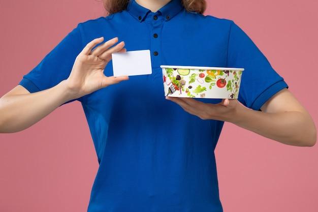 Weiblicher kurier der vorderansicht im blauen uniformumhang, der lieferschüssel mit karte auf hellrosa wand hält, service delivery-mitarbeiterjob