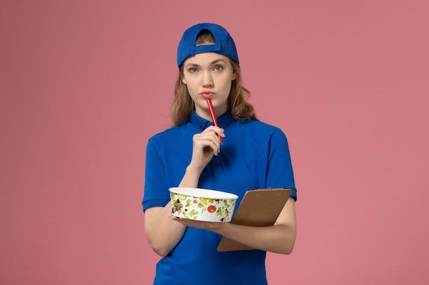 Weiblicher kurier der vorderansicht im blauen uniformumhang, der lieferschüssel und notizblock hält, die auf dem hellrosa schreibtischdienstlieferungsmitarbeiter schreiben
