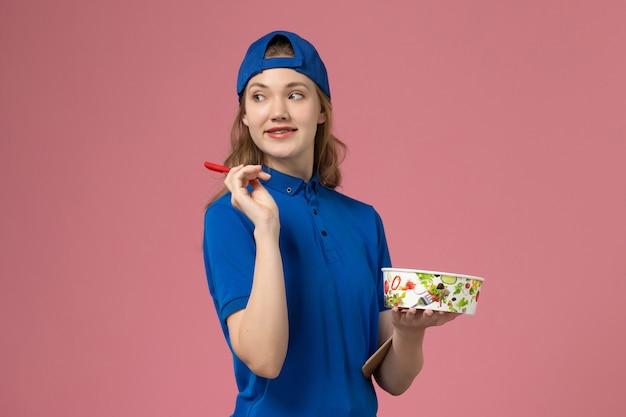 Weiblicher kurier der vorderansicht im blauen uniformumhang, der lieferschüssel und notizblock mit stift auf rosa wand hält, service-zustellungsmitarbeiter