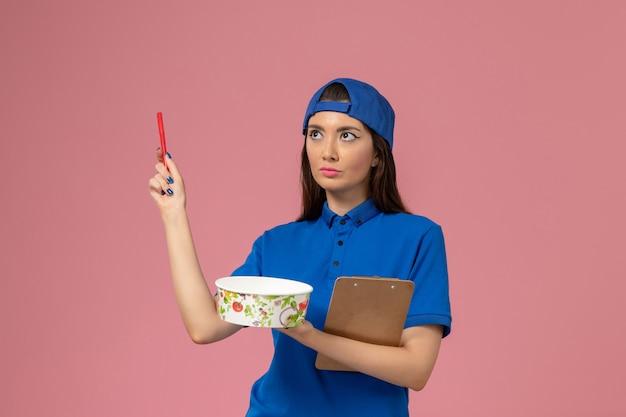 Weiblicher kurier der vorderansicht im blauen uniformumhang, der notizblock und stift mit lieferschüssel auf hellrosa wand hält, service-mitarbeiterzustellung