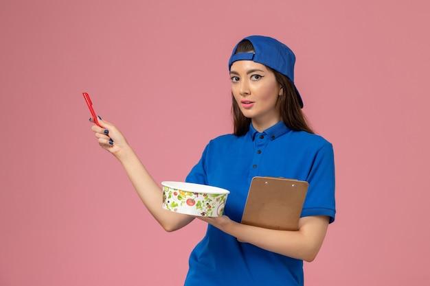 Weiblicher kurier der vorderansicht im blauen uniformumhang, der notizblock und stift mit lieferschüssel auf hellrosa wand hält, servicemitarbeiter-lieferarbeit