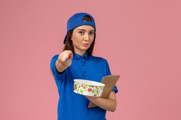 Weiblicher kurier der vorderansicht im blauen uniformumhang, der notizblock und stift mit lieferschüssel auf hellrosa wand hält, servicemitarbeiter-lieferarbeiter